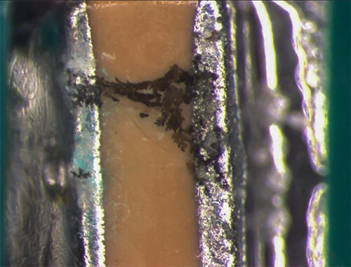 Dendritic grown between solder pads, caused by ionic contamination on printed circuit board
